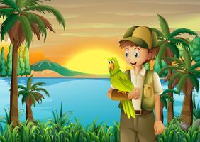 Ein Junge mit einem Papagei am Flussufer