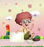 Ein Junge, der einen leeren Signage mit fliegenden Süßigkeitsbällen an der Rückseite anhält