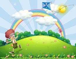 Ein Junge, der mit seinem Drachen am Hügel mit einem Regenbogen spielt vektor