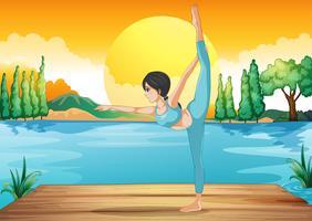Ein Mädchen, das Yoga entlang dem Fluss in einer Sonnenunterganglandschaft durchführt