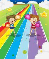 Två unga cheerleaders dansar på den färgglada vägen