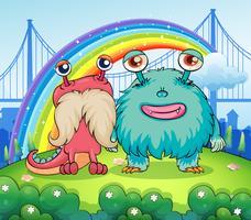 Två konstiga monster och en regnbåge i himlen