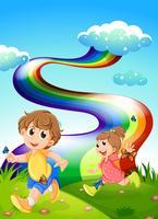 Kinder, die am Hügel mit einem Regenbogen im Himmel gehen
