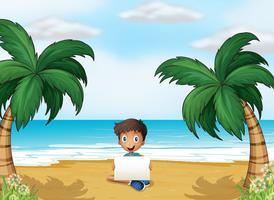 Ein Junge, der einen leeren Signage am Strand hält