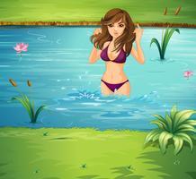 En tjej simmar vid dammen