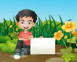 Ein lächelnder Junge, der einen leeren Signage im Garten hält
