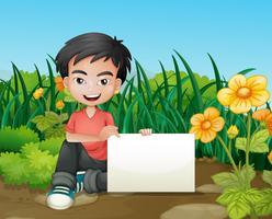 En leende pojke med en tom skyltning i trädgården