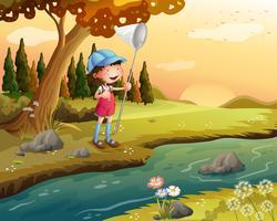 En tjej som håller ett nät längs floden