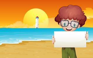 Ein Junge am Strand, der einen leeren Signage hält