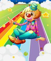 En kvinnlig clown sitter vid den färgglada vägen