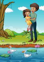 Ein junges Mädchen und ihr Vater am Flussufer