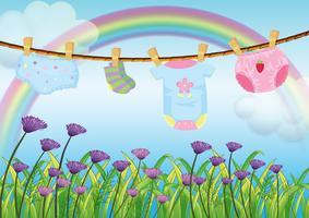 Ett barns kläder hänger över trädgården