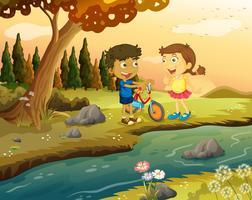 En pojke och en flicka med en cykel som står vid flodbredden vektor