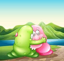 Ett grönt och ett rosa monster kramar varandra vid flodbredden