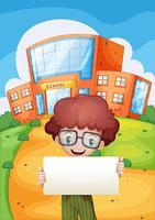 Ein Junge, der einen leeren Signage hält, der vor der Schule steht