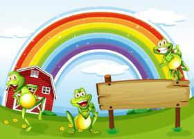 En tom träbräda med grodor och en regnbåge i himlen