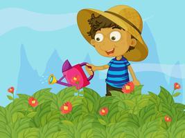 En pojke vattnar växterna i en trädgård