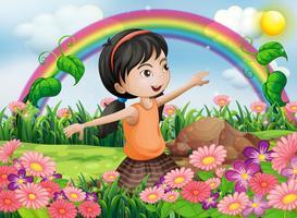 En glad tjej i trädgården med färska blommande blommor