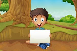 En pojke som håller en tom skylt nära det jätte trädet