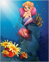Eine lächelnde Meerjungfrau, die über den Felsen sitzt