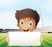 Ein lächelnder Junge, der einen leeren Signage am Fußballplatz hält