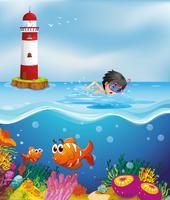 Ein Junge, der am Strand nahe dem Leuchtturm schwimmt