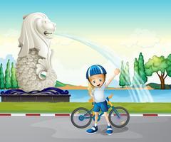 En ung cyklist nära statyn av Merlion vektor
