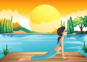 Ein Mädchen, das Yoga entlang dem Fluss durchführt