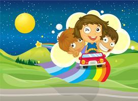 Tre barn rider på en bil som passerar över regnbågen