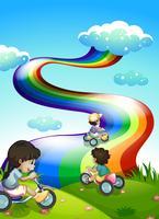 Kinder, die am Gipfel mit einem Regenbogen im Himmel spielen vektor
