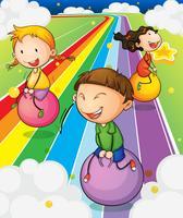 Tre barn leker med studsande bollar på den färgglada vägen