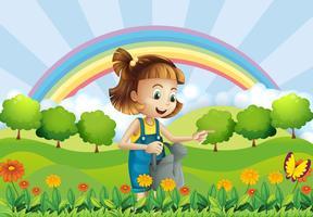 Ein junges Mädchen, das eine Berieselungsanlage im Garten hält