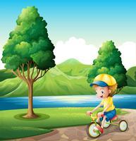 En pojke som leker med sin lilla cykel vektor