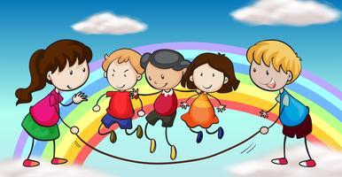 Fünf Kinder, die vor einem Regenbogen spielen