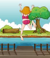 En tjej hoppar på träbroen