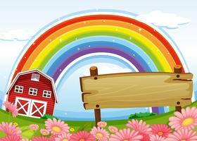 Ein leeres hölzernes Schild am Bauernhof und ein Regenbogen aufwärts
