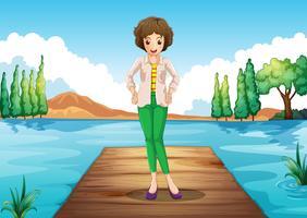Eine Frau, die über der Holzbrücke in dem Fluss steht