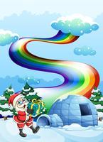 Santa Claus nahe dem Iglu und einem Regenbogen im Himmel