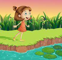 En liten flicka vid flodbredden vektor