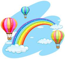 Tre ballonger som flyger över regnbågen