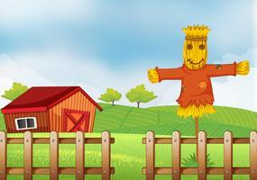 Eine Vogelscheuche im Holzzaun