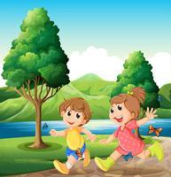 Glückliche und energische Kinder, die nahe dem Fluss spielen