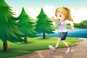 En tjej joggar nära tallarna vid flodbredden