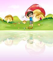 Ein Junge, der Golf am Flussufer spielt