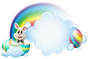 Ett knäckt ägg med en kanin nära regnbågen