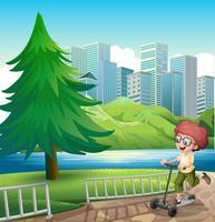 Ein glücklicher Junge, der mit seinem Roller nahe dem Fluss spielt