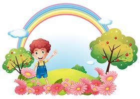 En pojke i backen med en regnbåge