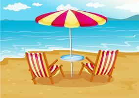 Ein Sonnenschirm mit Stühlen am Strand