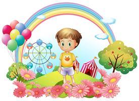 En ung pojke på kullen med en trädgård och en karneval