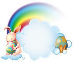 Ein Häschen, das ein Osterei nahe dem Regenbogen umarmt